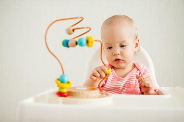 Kleines mädchen spielt mit einem pädagogischen labyrinthspielzeug. entwicklung der feinmotorik und logisch