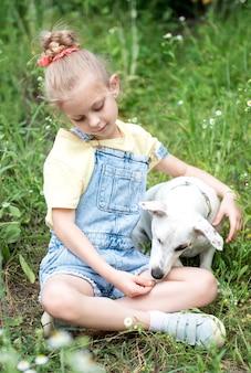 Kleines mädchen spielt mit einer hunderasse jack russell terrier