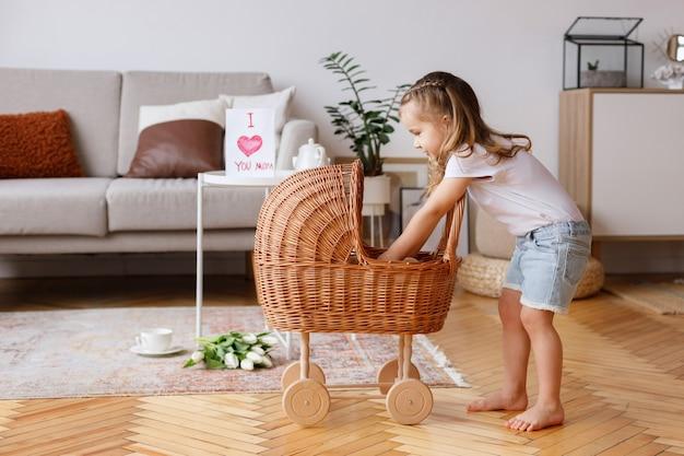 Kleines mädchen spielt mit kinderwagen im wohnzimmer