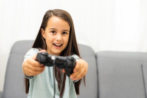 Kleines mädchen spielt mit playstation-joystick