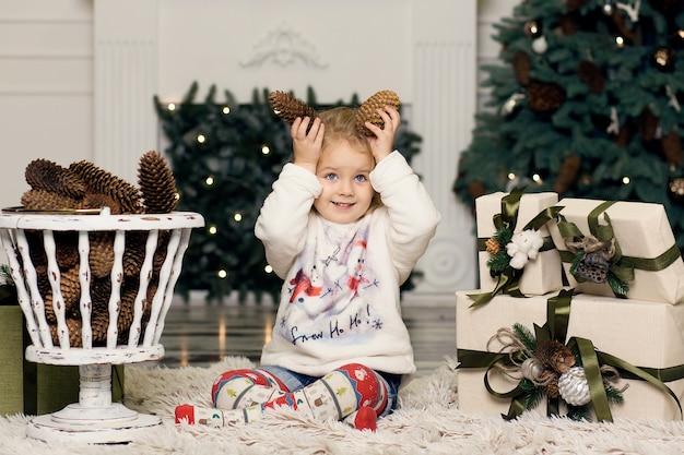 Kleines mädchen spielt mit tannenzapfendekorationen zum weihnachtsbaum