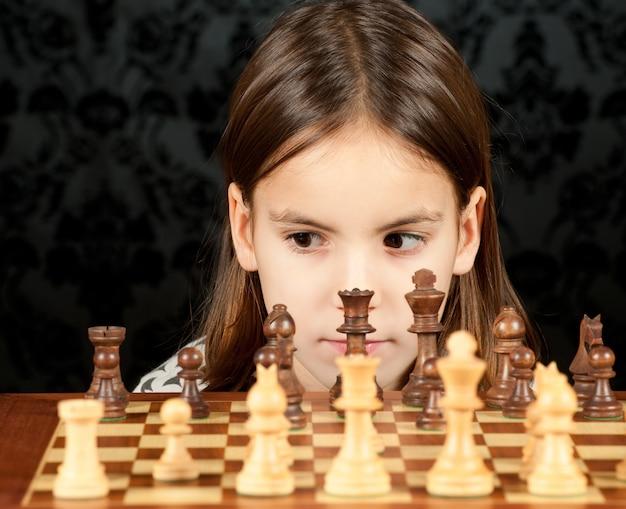 Kleines mädchen spielt schach auf vintage wand