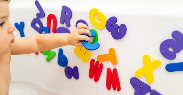 Kleines mädchen spielt schaumstoff im bad. abc mit spiel lernen. montessori-aktivität