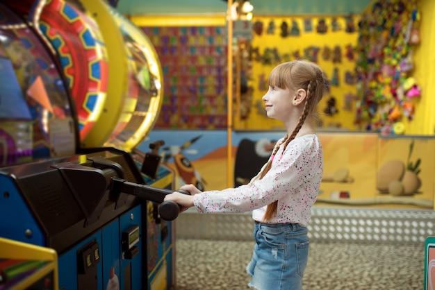 Kleines mädchen spielt spielmaschine, kinderzentrum