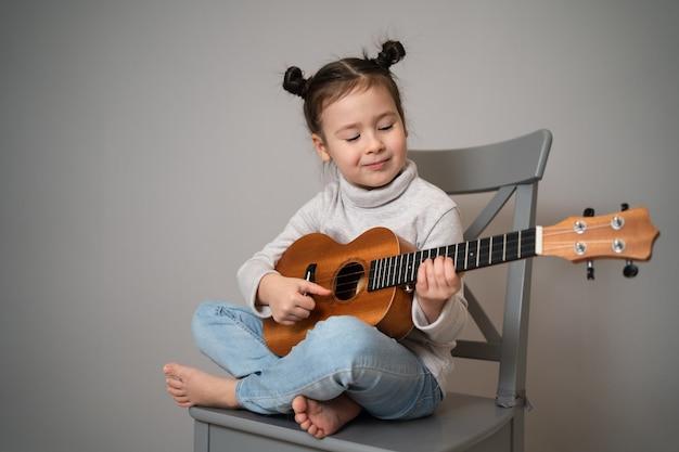 Kleines mädchen spielt ukulele. kreative entwicklung bei kindern. musikalische ausbildung von kindheit an. musik online zu hause unterrichten.
