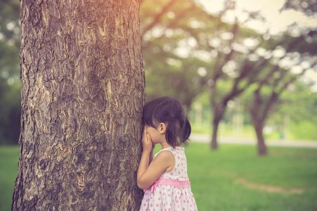 Kleines mädchen spielt versteckendes gesicht des versteckens im park. weinlesefarbe