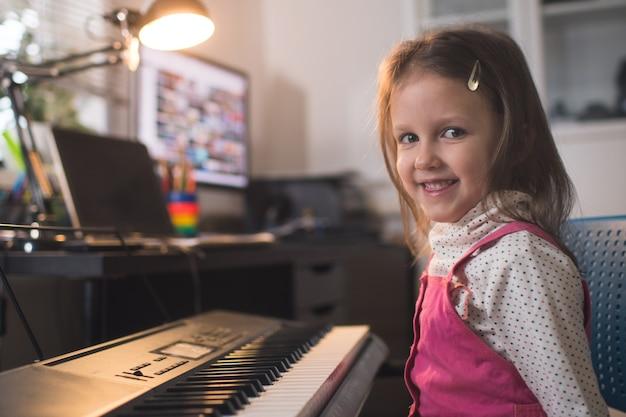 Kleines mädchen spielt zu hause in ihrem zimmer klaviersynthesizer