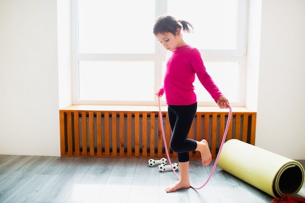Kleines mädchen springt zu hause auf ein seiltraining. süßes kind trainiert auf einer matte drinnen. das kleine dunkelhaarige weibliche model in sportbekleidung hat übungen in der nähe des fensters in ihrem zimmer