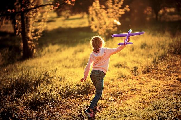 Kleines mädchen startet ein spielzeugflugzeug in die luft im park