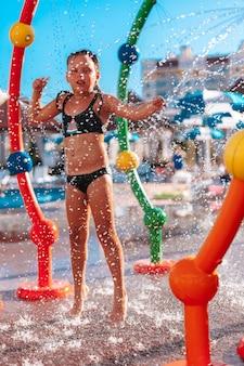 Kleines mädchen steht am pool glückliches schönes mädchen im schwarzen badeanzug im pool des wasserparks hat spaß...