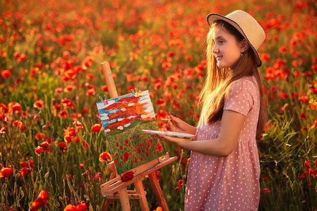 Kleines mädchen steht im feld der roten mohnblumen und malt auf der leinwand auf einem zeichenständer a
