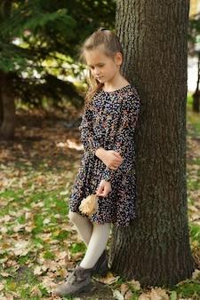 Kleines mädchen steht in einem stadtpark und hält eine gegossene eiche. herbstspaziergänge.