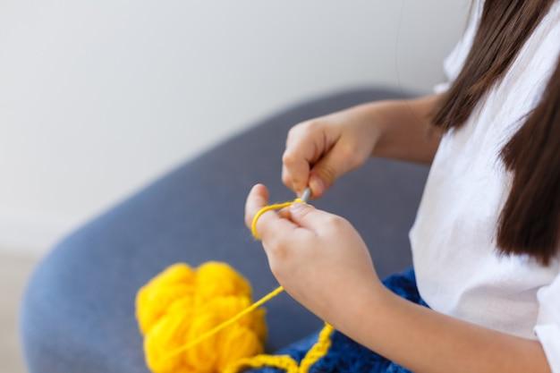 Kleines mädchen strickt häkeln. das mädchen sitzt auf der couch und strickt aus strickgarn. häkeln sie dicke fäden. wohnkomfort.