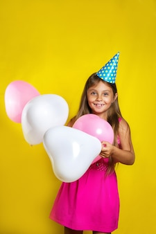 Kleines mädchen trägt einen partyhut an ihrem geburtstag. glückliches mädchen mit bunten ballonen