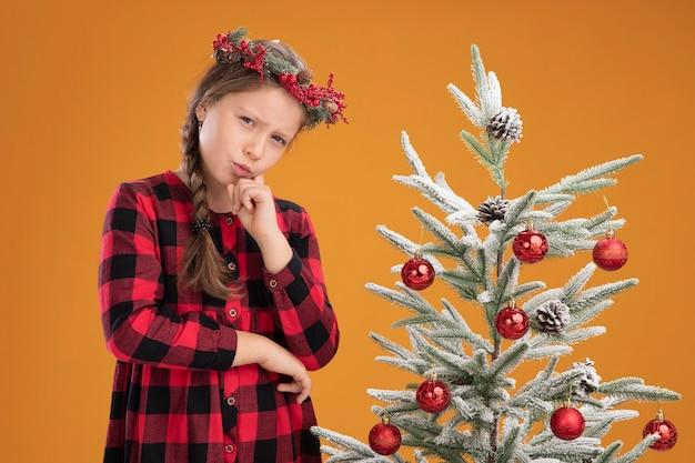 Kleines mädchen trägt weihnachtskranz in kariertem hemd mit hand am kinn und denkt mit ernstem gesicht, das neben einem weihnachtsbaum über oranger wand steht