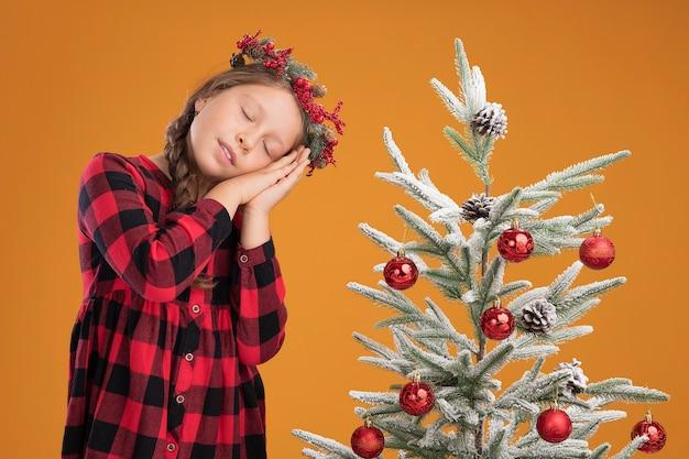 Kleines mädchen trägt weihnachtskranz in kariertem hemd und macht schlafgeste, die handflächen zusammenhält und den kopf auf handflächen mit geschlossenen augen neben einem weihnachtsbaum über orangefarbener wand lehnt
