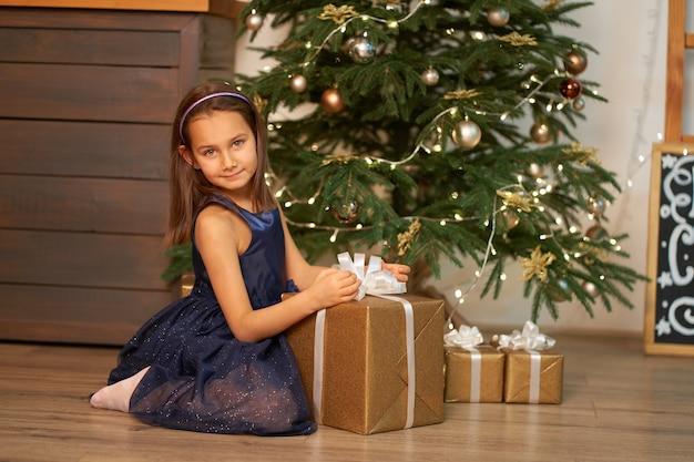 Kleines mädchen träumt, bevor es weihnachtsgeschenk für weihnachten öffnet