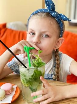 Kleines mädchen trinkt alkoholfreien mojito in einem café