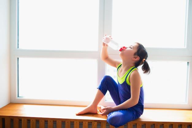 Kleines mädchen trinkt wasser nach dem training zu hause. nettes kind trainiert auf einer hölzernen fensterbank drinnen. kleines dunkelhaariges weibliches model