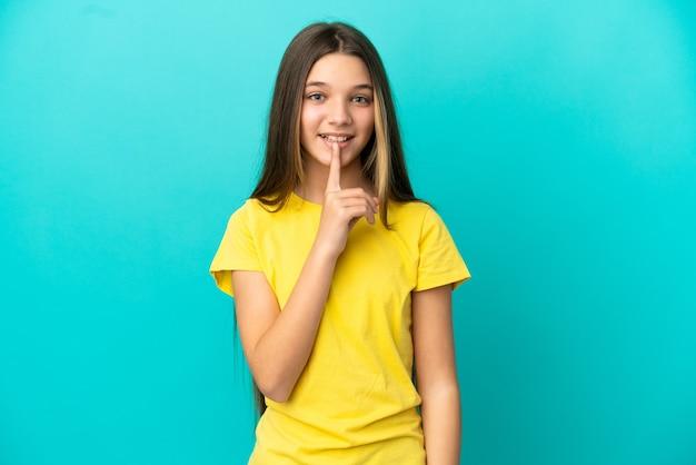 Kleines mädchen über isoliertem blauem hintergrund, das ein zeichen der stille zeigt, geste, die finger in den mund steckt