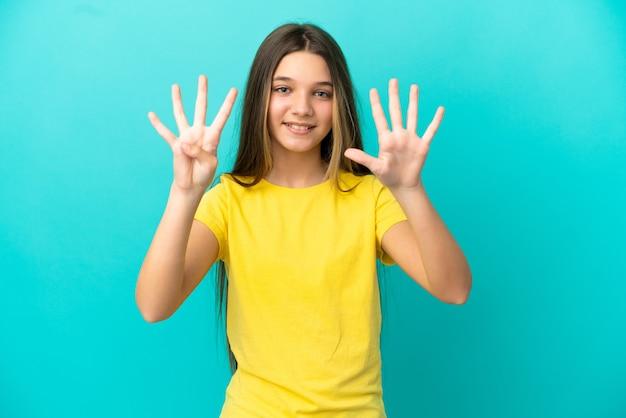 Kleines mädchen über isoliertem blauem hintergrund, das neun mit den fingern zählt