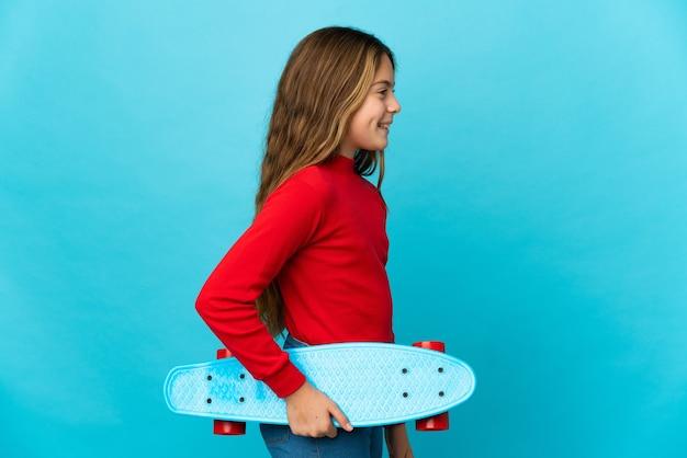 Kleines mädchen über isoliertem blauem hintergrund mit einem skate