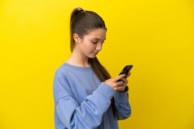 Kleines mädchen über isoliertem gelbem hintergrund, das eine nachricht oder e-mail mit dem handy sendet