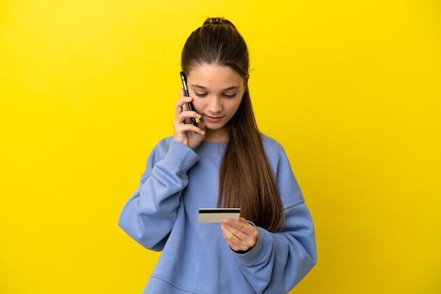 Kleines mädchen über isoliertem gelbem hintergrund, das mit dem handy mit einer kreditkarte kauft