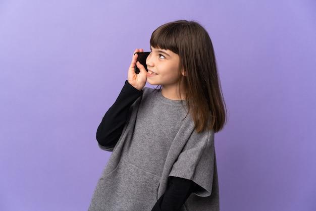 Kleines mädchen über isoliertem hintergrund, das mit jemandem ein gespräch mit dem mobiltelefon führt