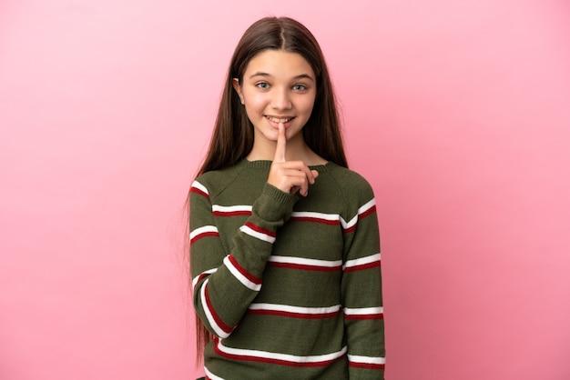 Kleines mädchen über isoliertem rosa hintergrund, das ein zeichen der stille zeigt, geste, die finger in den mund steckt