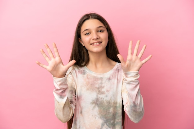 Kleines mädchen über isoliertem rosa hintergrund, das mit den fingern zehn zählt
