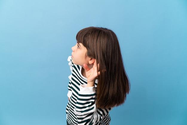 Kleines mädchen über isolierter wand, die etwas hört, indem man hand auf das ohr legt