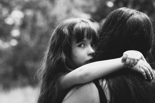 Kleines mädchen umarmt ihre mutter