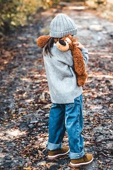 Kleines mädchen umarmt ihren bären auf einem hintergrund der natur, herbst, durba.