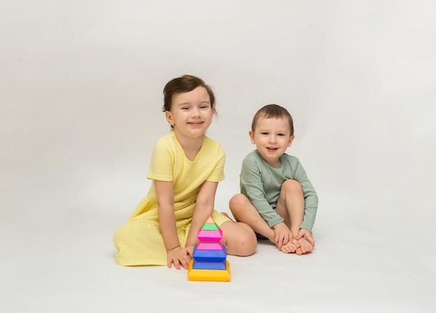 Kleines mädchen und ein junge spielen mit einer bunten pyramide und betrachten die kamera auf einem weißen hintergrund
