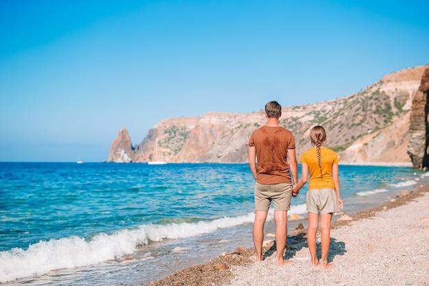 Kleines mädchen und glücklicher vater, der spaß während des strandurlaubs hat