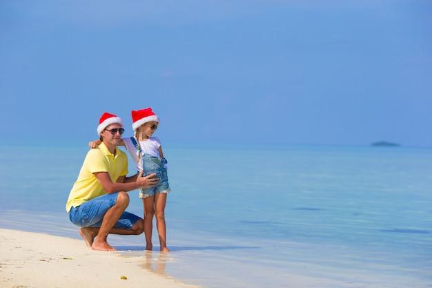 Kleines mädchen und glücklicher vati in santa hat während der strandferien