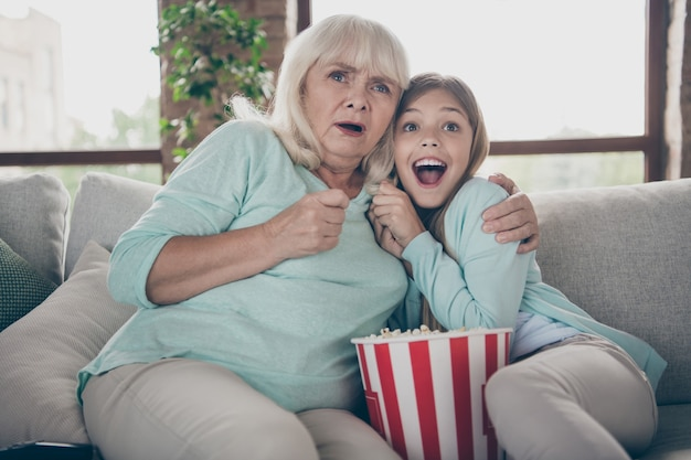 Kleines mädchen und großmutter sitzen auf der couch