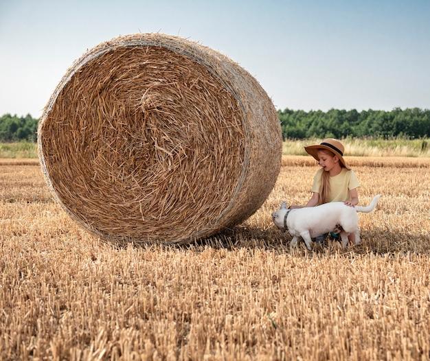 Kleines mädchen und hund, die sich an einem sommertag auf einem weizenfeld amüsieren. kind, das während der erntezeit am heuballenfeld spielt.