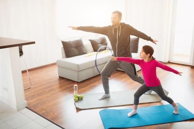 Kleines mädchen und ihr junger vater machen zu hause longe-forward-training. nettes kind trainiert drinnen. kleines dunkelhaariges weibliches modell in sportbekleidung hat übungen im zimmer.