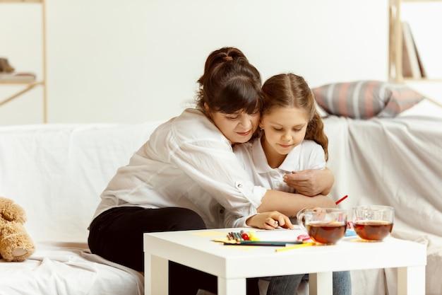 Kleines mädchen und ihre charmante großmutter sitzen auf dem sofa und verbringen zeit zusammen zu hause. generation von frauen. internationaler frauentag. schönen muttertag.