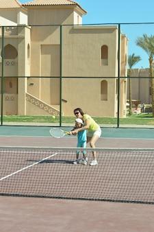 Kleines mädchen und ihre mutter beim tennisspielen