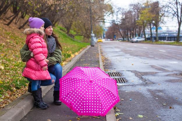 Kleines mädchen und ihre mutter, die mit regenschirm an einem regnerischen tag geht