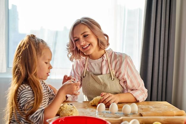 Kleines mädchen und ihre mutter in der schürze kneten den teig in der küche, hausgemachtes gebäck für brot, pizza oder kekse backen. familienspaß und kochkonzept