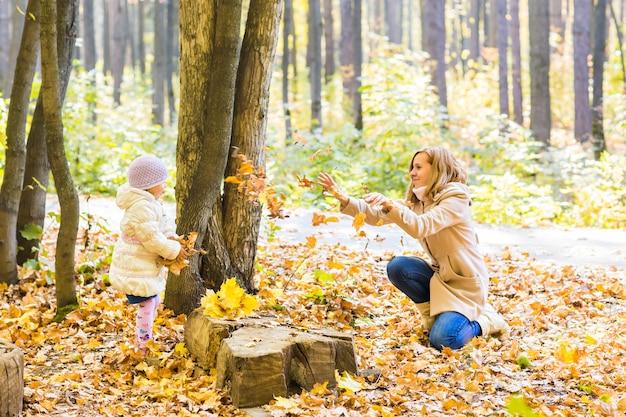 Kleines mädchen und ihre mutter spielen im herbstpark.