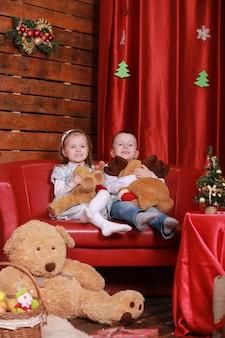 Kleines mädchen und junge auf sofa im weihnachtsstudio in den roten farben. weihnachtsbaum und teddybär an der wand.