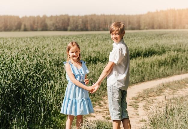 Kleines mädchen und junge, bruder und schwester, die an einem sonnigen tag händchen in der natur halten. kinder auf dem land.