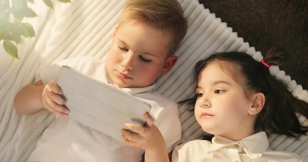 Kleines mädchen und junge, der digitale tablette verwendet