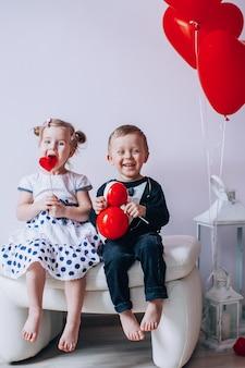 Kleines mädchen und junge, die auf einem weißen stuhl nahe heart-shaped baloons sitzt. mädchen, das einen roten lutscher leckt. valentinstag-konzept.