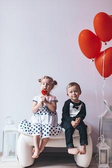 Kleines mädchen und junge, die auf einem weißen stuhl nahe herz-förmigen ballonen sitzt.